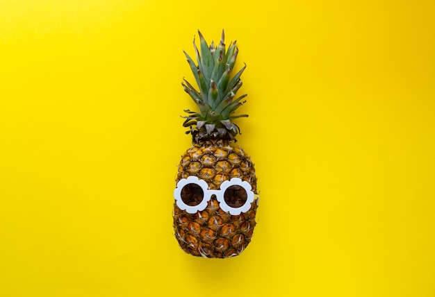Pineapple in white sunglasses on the colorful background, creative summer concept