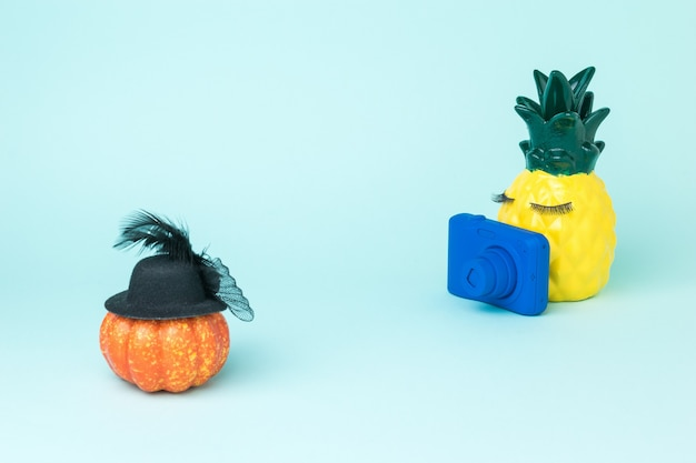 Pineapple with a blue camera takes pictures of a pumpkin. fun photo shooting.