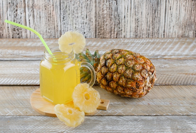 Pineapple with candied rings, juice on wooden surface