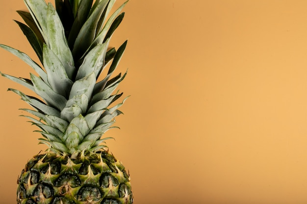 Pineapple with green leaves on a orange color wall