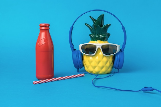 Pineapple with headphones and glasses and a bottle of refreshing drink on a blue background. summer concept.