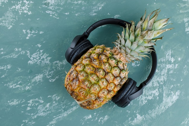 Pineapple with headphones on plaster surface