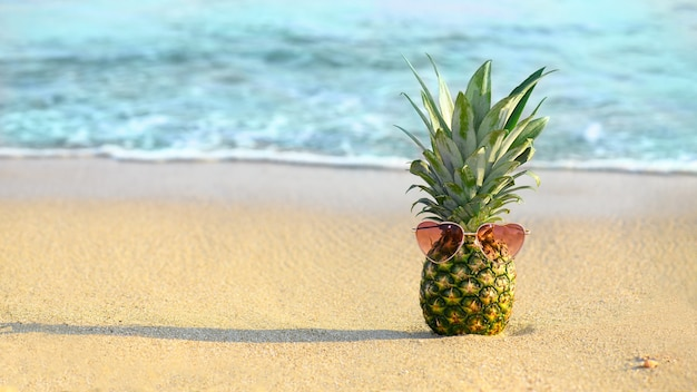Pineapple with heat shape sanglasses on the beach