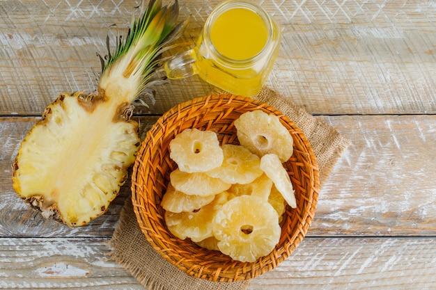 ジュースと木製の表面に砂糖漬けのリングとパイナップル