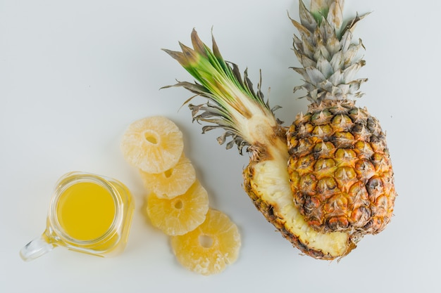 Pineapple with juice and candied rings on white surface