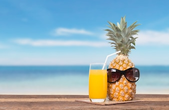 Pineapple with juice On the beach table and the blue sky for summer concept