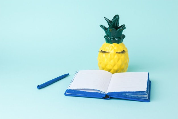 Pineapple with a pen in front of an open notebook on a blue background. the concept of record keeping.
