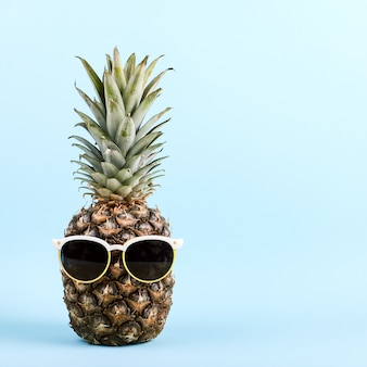 Pineapple with sunglasses, the concept of a funny summer mood on blue