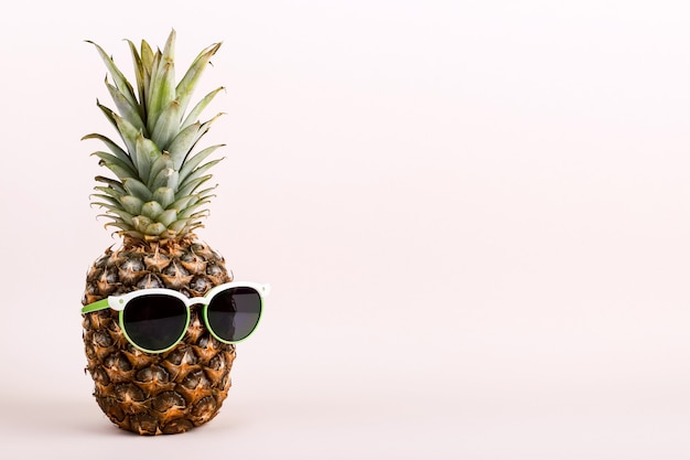 Pineapple with sunglasses, concept of a funny summer mood.