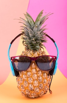 Pineapple with sunglasses and headphone on orange background. fruit summer concept.