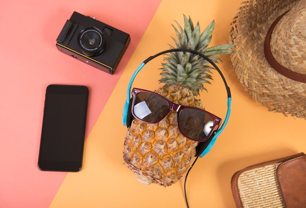 Pineapple with sunglasses and headphone on orange background