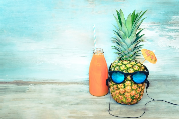 Pineapple with sunglasses and headphones and a bottle of juice in front of a blue wood