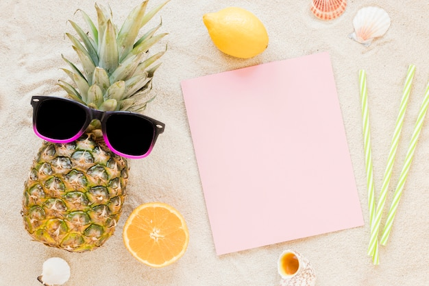 Pineapple with sunglasses and paper on sand