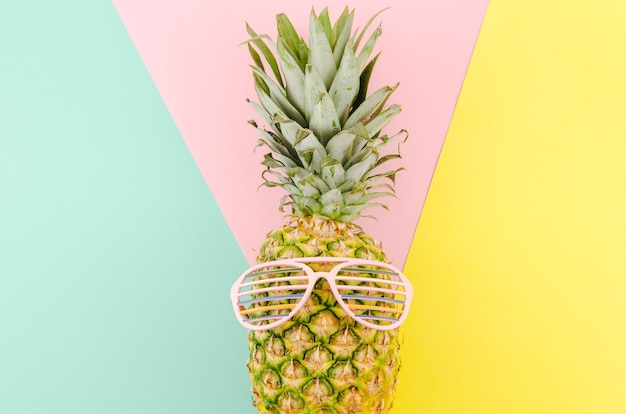 Pineapple with sunglasses on table