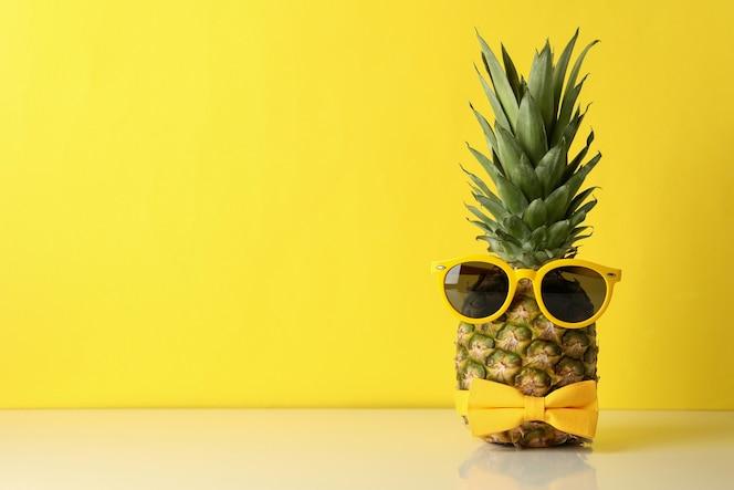 ananas con fiocco cravatta e occhiali da sole su sfondo giallo