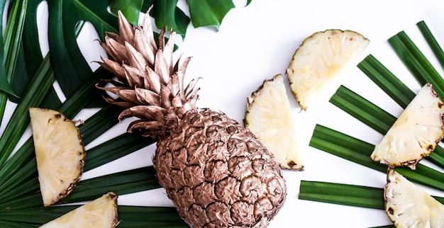 白い背景の上の熱帯の葉とパイナップル