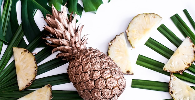 Pineapple with tropical leaves on white background