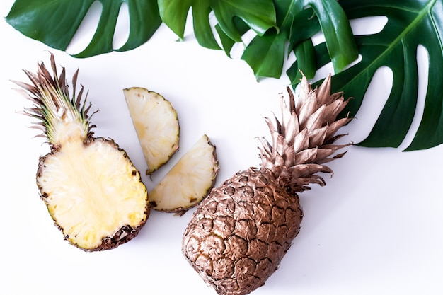 Pineapple with tropical leaves on white table