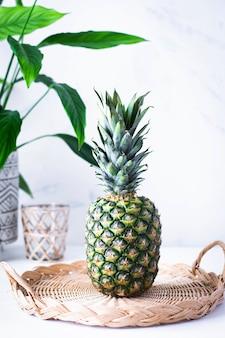 Ananas nel piatto di bambù intrecciato sulla tavola bianca