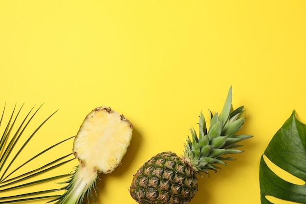 Ананасы и пальмовые листья на желтом фоне, место для текста