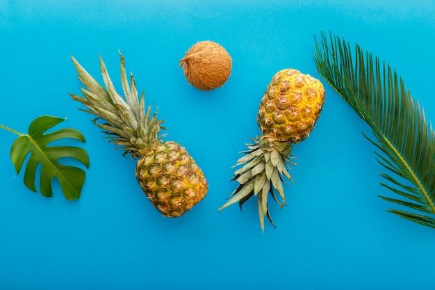 黄色の夏の背景にパイナップルとヤシの葉。トロピカルサマーパイナップルフルーツフラットレイ組成物。高品質のストックフォト