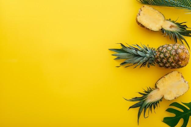 黄色の夏の背景にパイナップルとヤシの葉。熱帯の夏のパイナップルの果実全体とスライスされたパイナップルの半分は、コピースペースを備えたフラットレイ構成です。