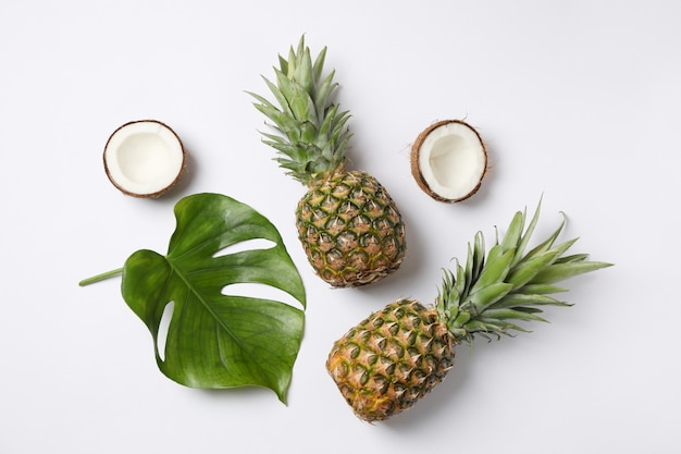 Pineapples, coconuts and palm leaves on white background