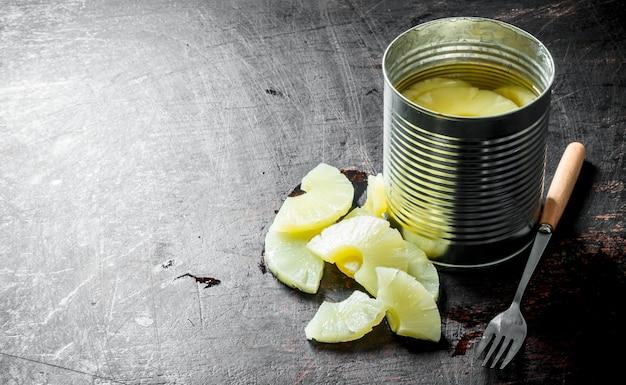 黒い木製のテーブルの上のブリキ缶のパイナップル