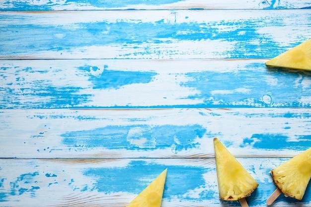 Ананасы на палочках от мороженого на деревянных фоне