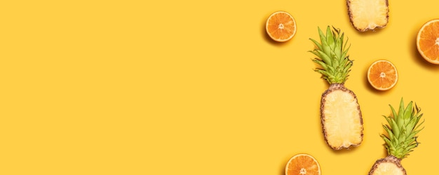 Pineapples, oranges, lemons, coconuts on yellow background.