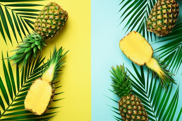 Pineapples, palm leaves on pastel colorful yellow and turquoise background with copy space.