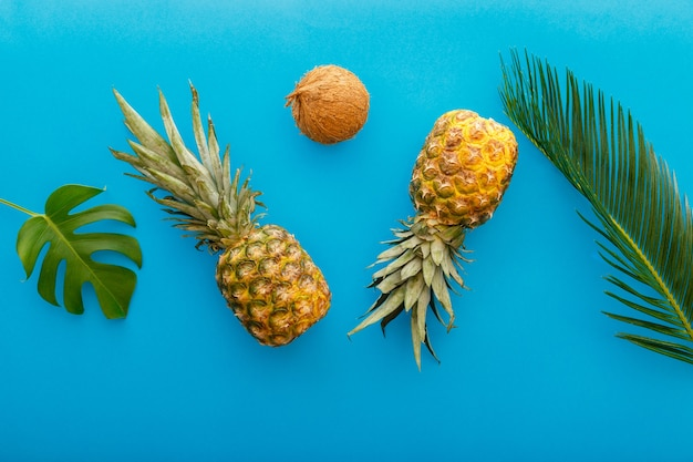 Pineapples and palm leaves on yellow color summer background. tropical summer pineapples fruits flat lay composition. high quality stock photo