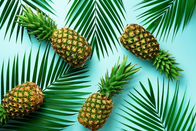 Pineapples and tropical palm leaves on pastel turquoise background. summer concept.