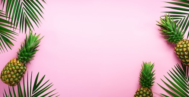 Pineapples and tropical palm leaves on punchy pastel pink background. summer concept.