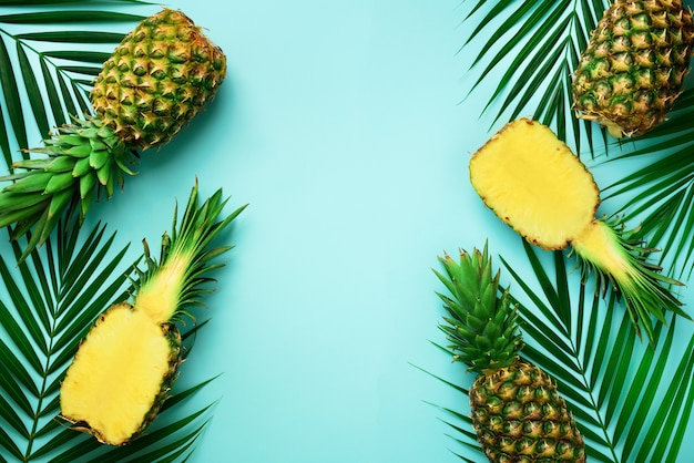 Pineapples and tropical palm leaves on punchy pastel turquoise background. summer concept. creative flat lay with copy space.