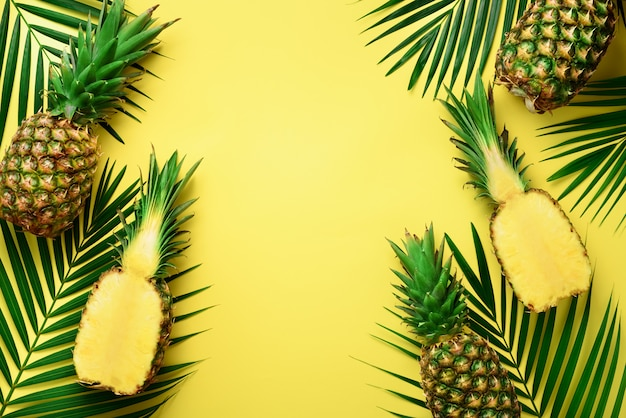 Pineapples and tropical palm leaves on punchy pastel yellow background. summer concept