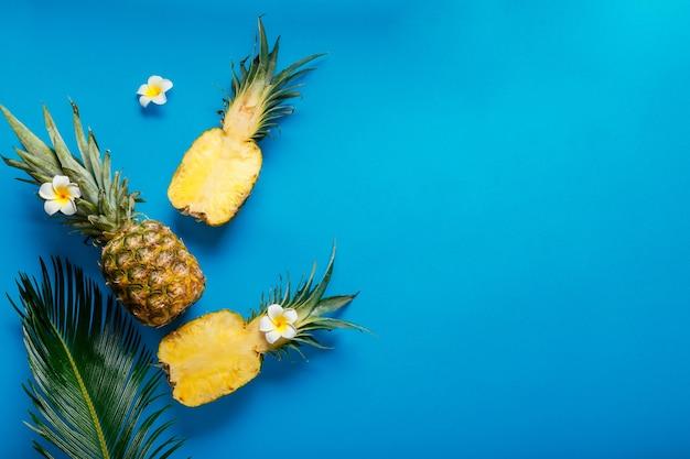 파인애플 전체 열대 여름 파인애플 과일과 파란색 여름 배경에 열대 플루메리아 꽃이 있는 얇게 썬 파인애플 반쪽. 복사 공간이 있는 평평한 위치. 고품질 스톡 사진