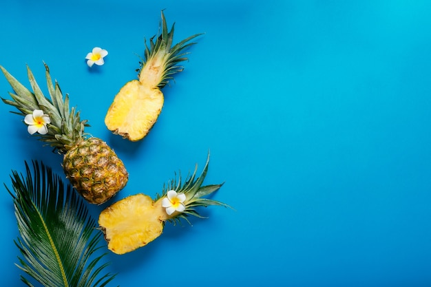 Pineapples whole tropical summer pineapples fruits and sliced pineapple halves with tropical plumeria flowers on blue color summer background. flat lay with copy space. high quality stock photo