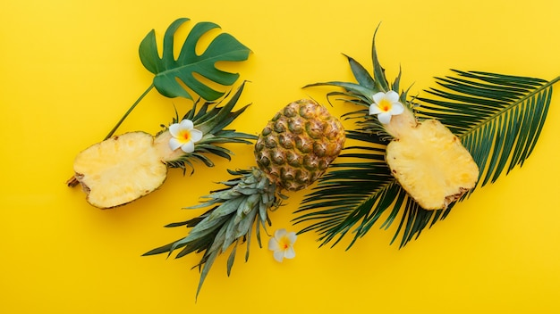 Pineapples whole tropical summer pineapples fruits and sliced pineapple halves with tropical plumeria flowers flat lay composition on yellow color summer background. long web banner.