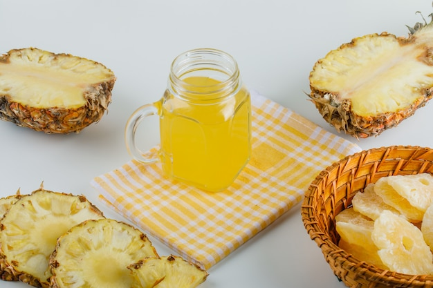 Pineapples with juice and candied rings on checkered kitchen towel