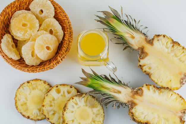 Pineapples with juice and candied rings on white surface