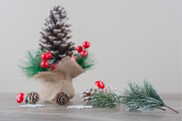 Pinecone decorated with holly berries and branches on marble table.