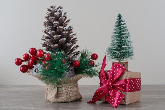 Pigna decorata con bacche di agrifoglio e sacchetto regalo sul tavolo di marmo.