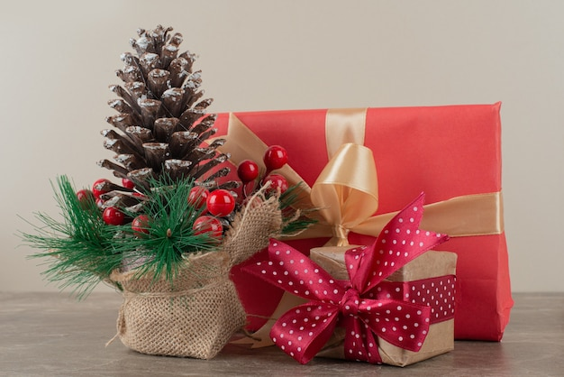 Pinecone decorated with holly berries and gift bags on marble table