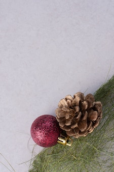 Pinecone with christmas ball on white surface