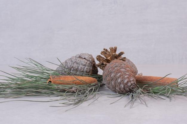 白いテーブルの上に木の緑の枝を持つ松ぼっくり。