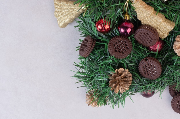 Pinecones with christmas balls and cookie on white surface