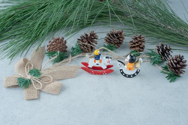 大理石の背景に小さなクリスマスのお祝いのおもちゃと松ぼっくり。高品質の写真