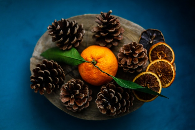 Pinecones on the wooden tray with tangerine on the blue armchairr