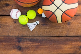 Ping-pong ball; baseball; shuttlecock; basketball and tennis ball on wooden plank